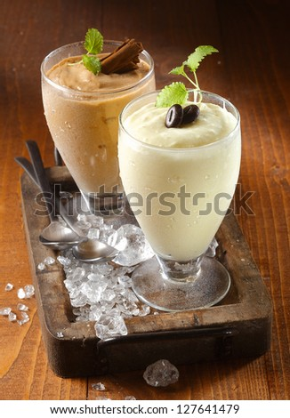 Two tall glasses of chilled thick creamy milkshake dessert or frappe topped with chocolate and mint on an old wooden tray with ice - stock photo