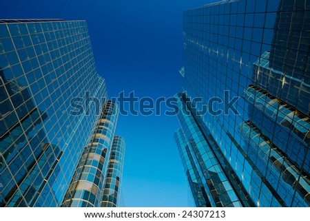 Two Tall Modern Financial Buildings with Glass Windows and Blue Sky