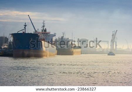 Two tankers in the harbour at sunrise - stock photo