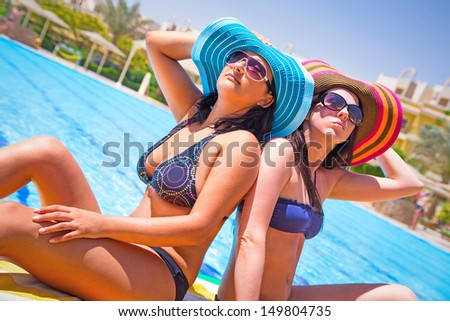 Two tanned girls relaxing at swimming pool