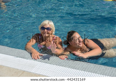 Two tanned women, senior blonde mother and mid adult brunette daughter are splashing in bright blue water at the edge of swimming pool.