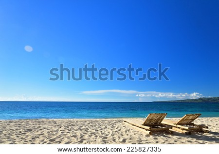 Two tanning beds at tropical sandy beach -- Vacations and Tourism concept  - stock photo