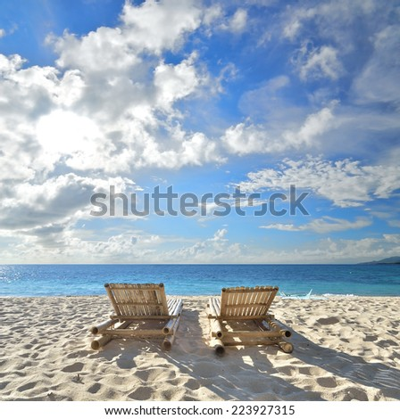 Two tanning beds on the tropical beach -- Tropical vacations concept - stock photo
