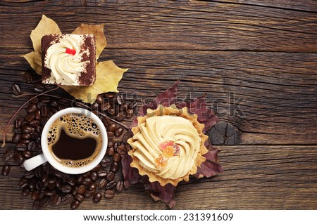 Two tasty cakes and cup of hot coffee on dark wooden table. Top view - stock photo