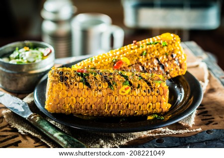 Two tasty grilled corncobs seasoned with herbs and butter for a delicious midday snack in a rustic kitchen - stock photo