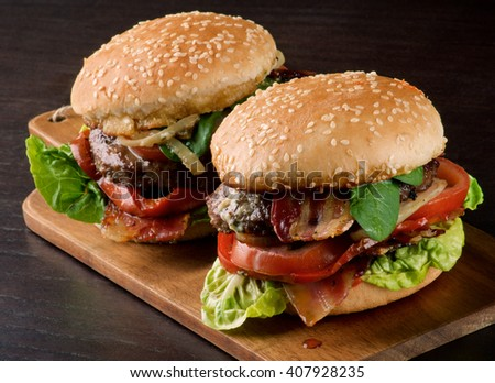 Two Tasty Hamburgers with Beef, Bacon, Lettuce, Tomatoes, Basil, Roasted Onion and Juicy Sauce on Sesame Buns In a Row closeup on Wooden Cutting Board - stock photo