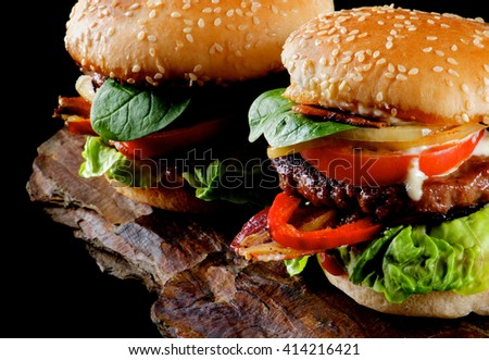 Two Tasty Hamburgers with Beef, Bacon, Lettuce, Tomatoes, Basil, Roasted Onion and Juicy Sauce on Sesame Buns Cross Section on Stone Board  - stock photo