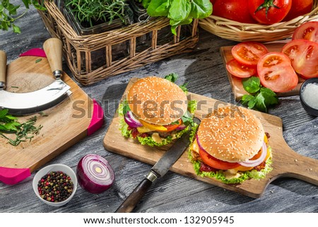 Two tasty homemade burgers and vegetables - stock photo
