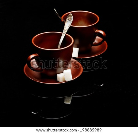 Two tea cups with teaspoons