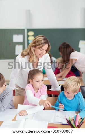 Two teachers working in a primary school with a class of young children helping them with their class work, focus to a female teacher with a small boy and girl - stock photo