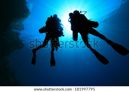 Two Tech Divers using rebreathers silhouette - stock photo