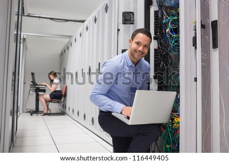 Two technicians doing data storage with their laptops - stock photo