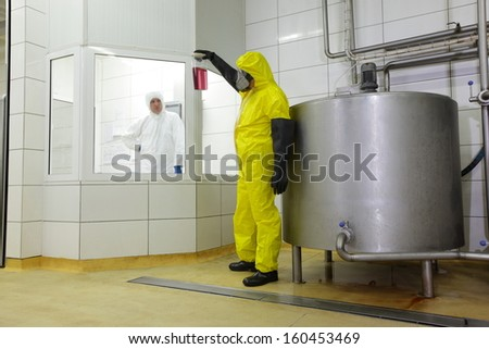 two technicians in protective uniforms working in industrial environment