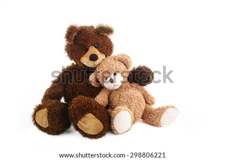 Two teddy bears, bigger and smaller, are sitting close to each other like they are best friends. - stock photo