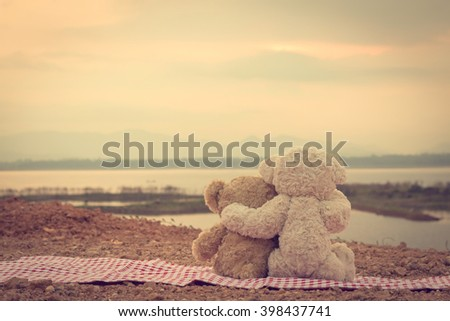 Two teddy bears hugging. picnic sit on the fabric red and white looking sunrise in the morning. - stock photo