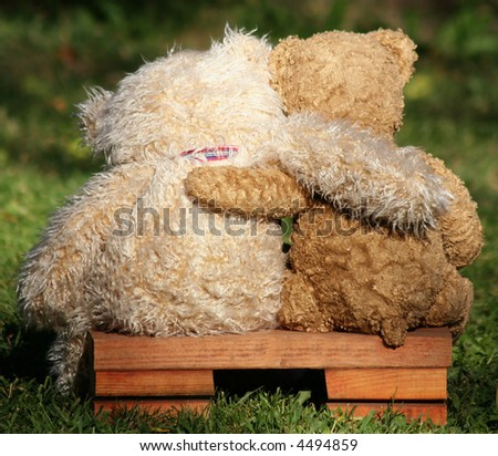 two teddy bears on a bench with arms around each other - stock photo