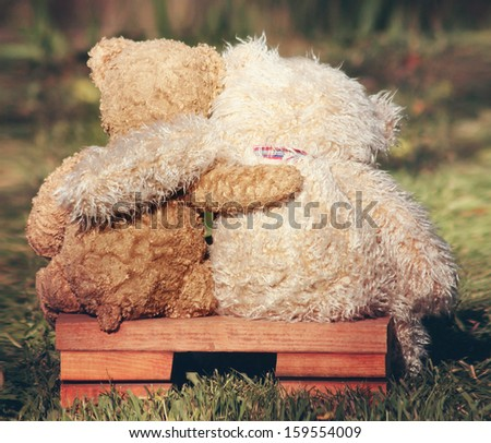 two teddy bears on a bench with arms around each other vintage toned - stock photo