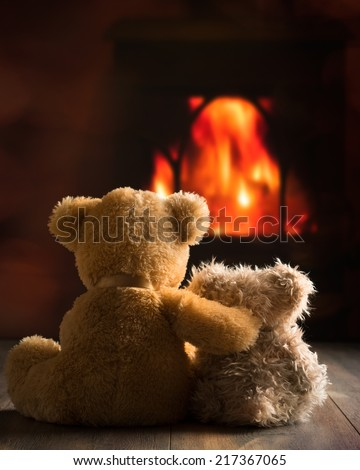 Two teddy bears sitting by the fire