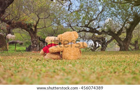 Two teddy bears sitting in the garden. Concept about love and relationship. - stock photo