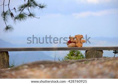 Two teddy bears sitting on the beautiful garden with love. Concept about love and relationship - stock photo