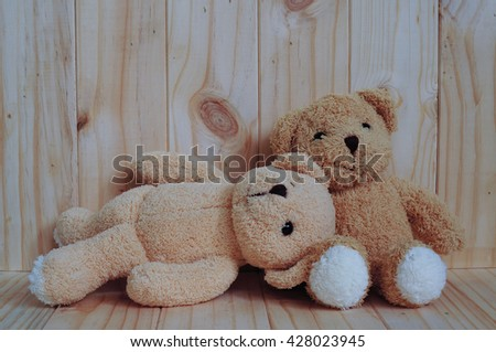 Two teddy bears sitting together on wooden background. Snuggle. Friendship concept. Love concept. Greeting card on wood. - stock photo