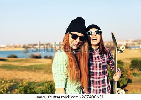 Two teen girl friends having fun together with skate board. Outdoors, urban lifestyle. Photo toned style Instagram filters. - stock photo