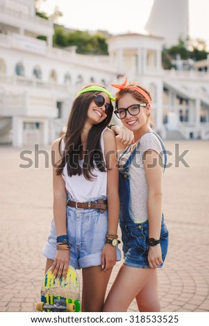 Two teen girl friends having fun together with skate board. Outdoors, urban lifestyle. Toned. Two beautiful and young girlfriends having fun with a skateboard.