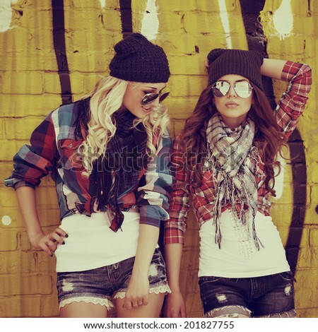 Two teen girl friends together having fun. Outdoors, urban lifestyle. Toned. - stock photo