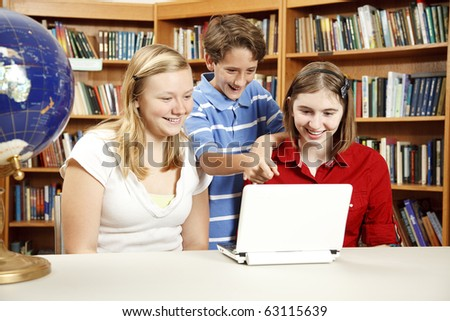 Two teen girls and a younger boy using a netbook computer in the school library. - stock photo