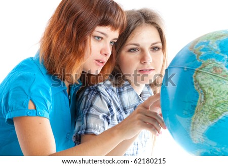 Two teen-girls are looking at globe. Isolated on white background