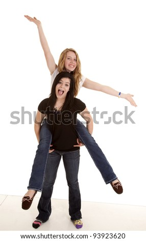 two teen girls having some fun goofing around with smiles on their faces. - stock photo