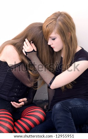Two teen girls huddling together against a building, as if one is in emotional pain. - stock photo