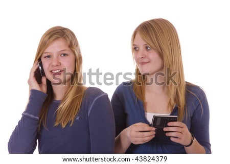Two teen girls on their cell phone, talking and texting.