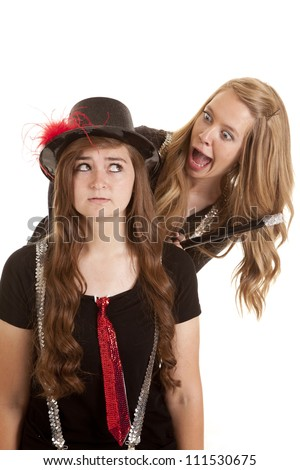 Two teen girls one is in a top hat and the other has a cane with silly expressions on their faces. - stock photo