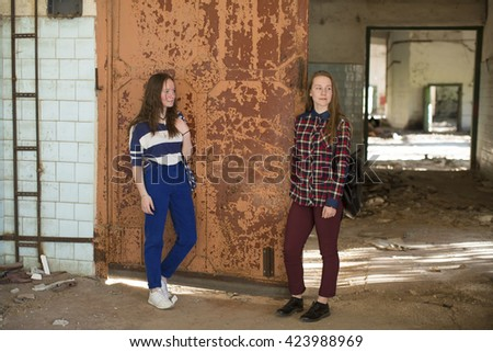Two teen girls standing at the old iron door in an abandoned building. - stock photo