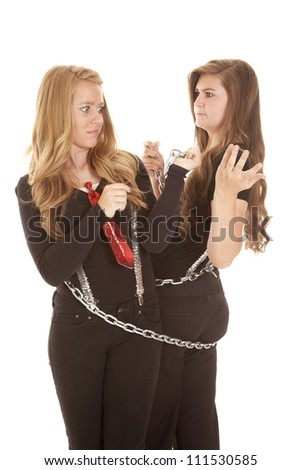 Two teen girls with funny expressions on their faces chained together - stock photo