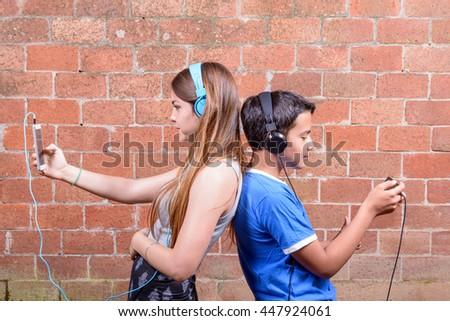 Two teen using smart phone but do not communicate with each other. / Two Teenager with Smart phones - stock photo