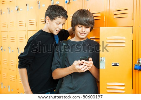 Two teenage boys playing a handheld video game in school by their lockers. - stock photo