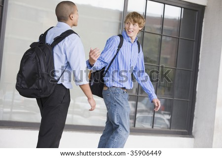 Two teenage boys wearing backpack and talking to each other - stock photo