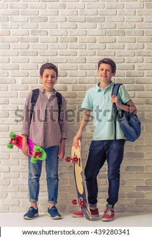 Two teenage boys with school backpacks and skateboards are looking at camera and smiling, standing against white brick wall - stock photo