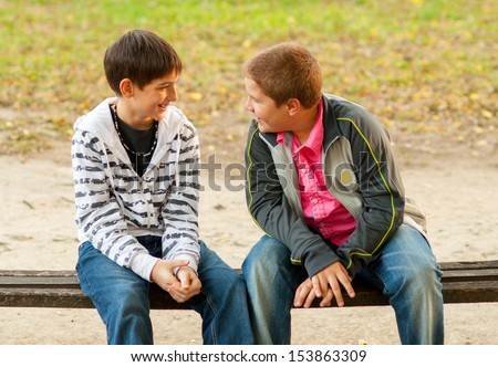 Two teenage friends talking while sitting on the bench in the park - stock photo