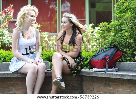 Two teenage girl friends sitting in front of a high school building on a bench talking and socializing with each other with their bags beside them. - stock photo