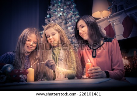 two teenage girls and a woman with christmas lights at home - stock photo
