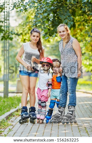 Two teenage girls and two kids in rollers stand together on walkway in park - stock photo