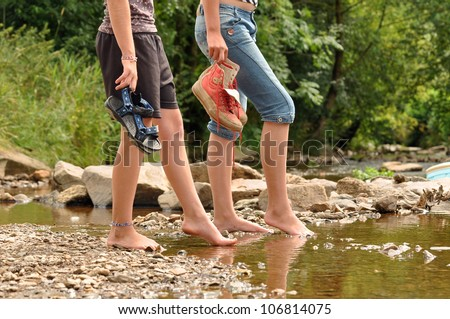 Two teenage girls cooling off their feet in a creek in the Belgian Ardennes - stock photo