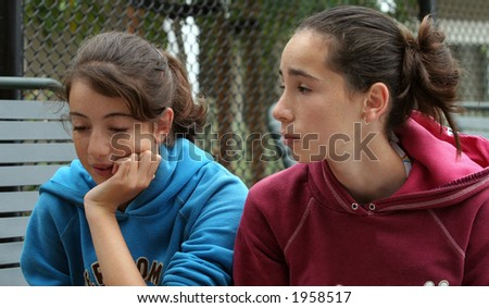 Two teenage girls discussing their problems outdoors - stock photo