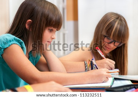 Two teenage girls doing homework at desk. - stock photo