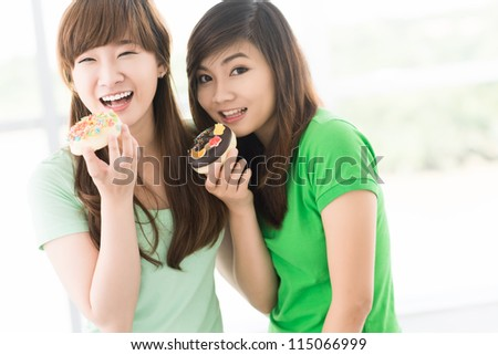 Two teenage girls eating sweet buns - stock photo