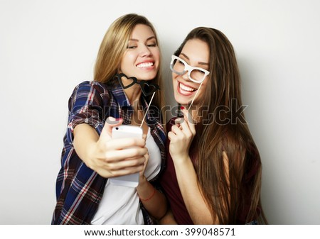 Two teenage girls friends in hipster outfit make selfie