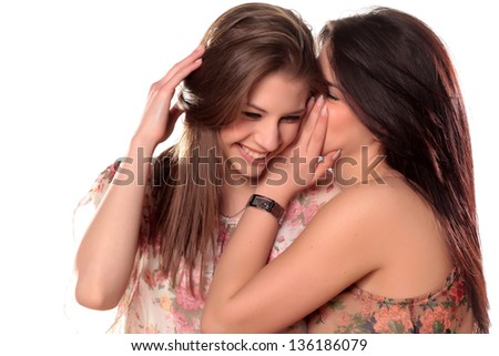 Two teenage girls gossiping and laughing - stock photo